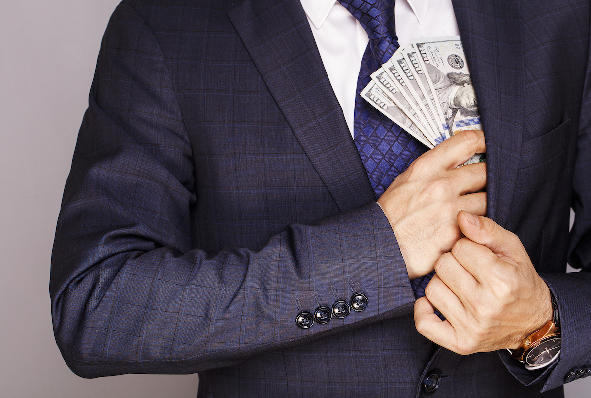 Man putting money in suit pocket 2